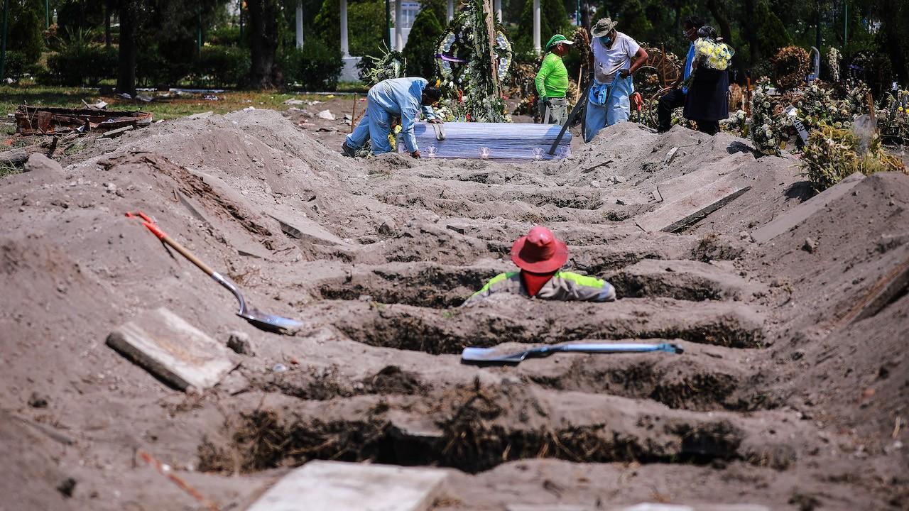 Trabajadores del cementerio entierran el ataúd con los restos de una víctima de covid en CDMX (Getty Images)