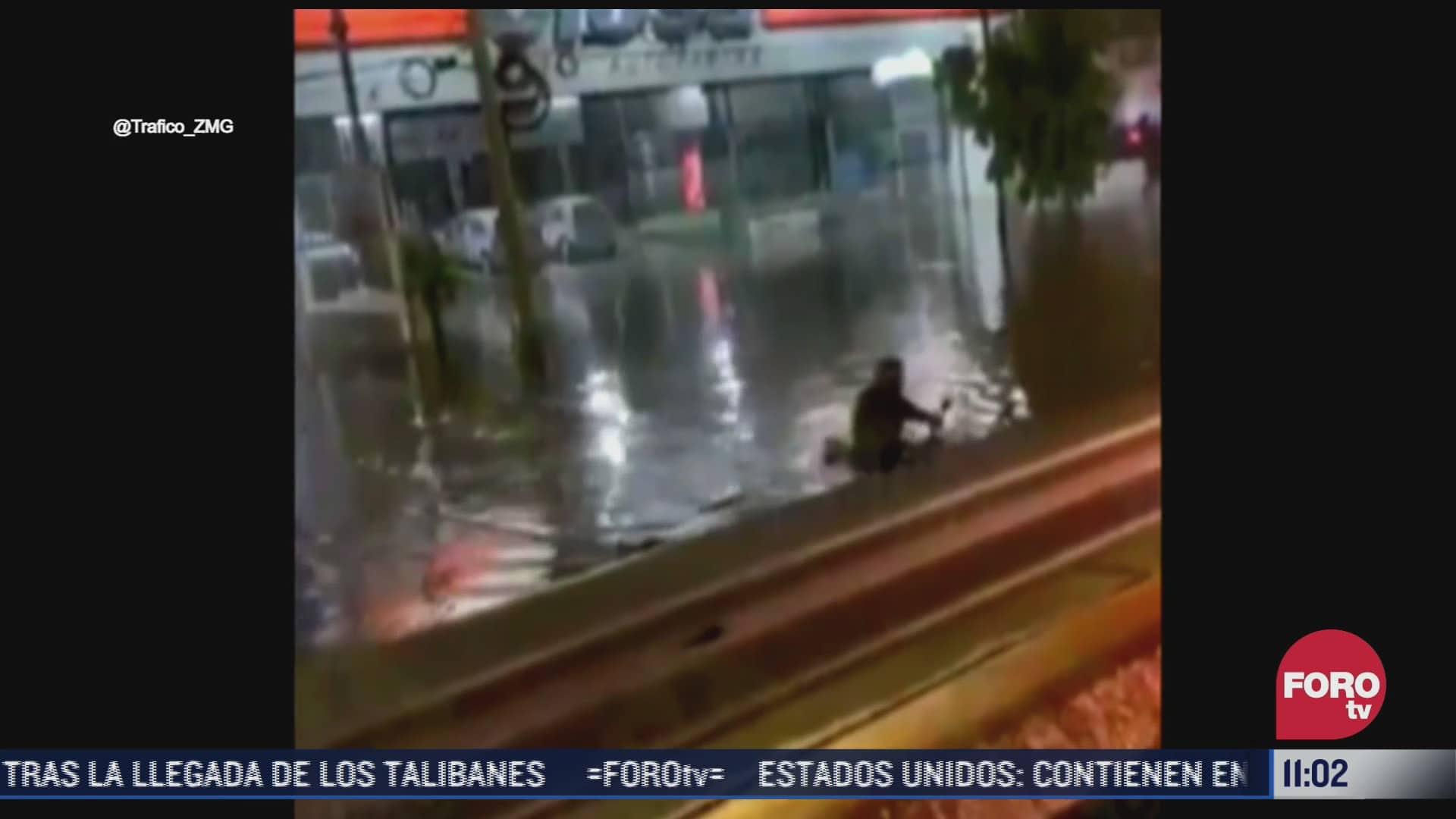 motociclista intenta cruzar avenida inundada en guadalajara jalisco