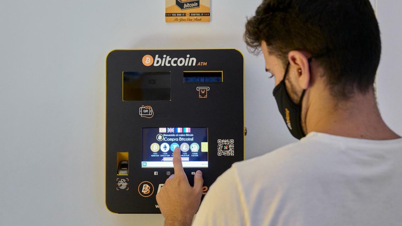 Una persona realiza transacciones con una maquina de criptomonedas.
