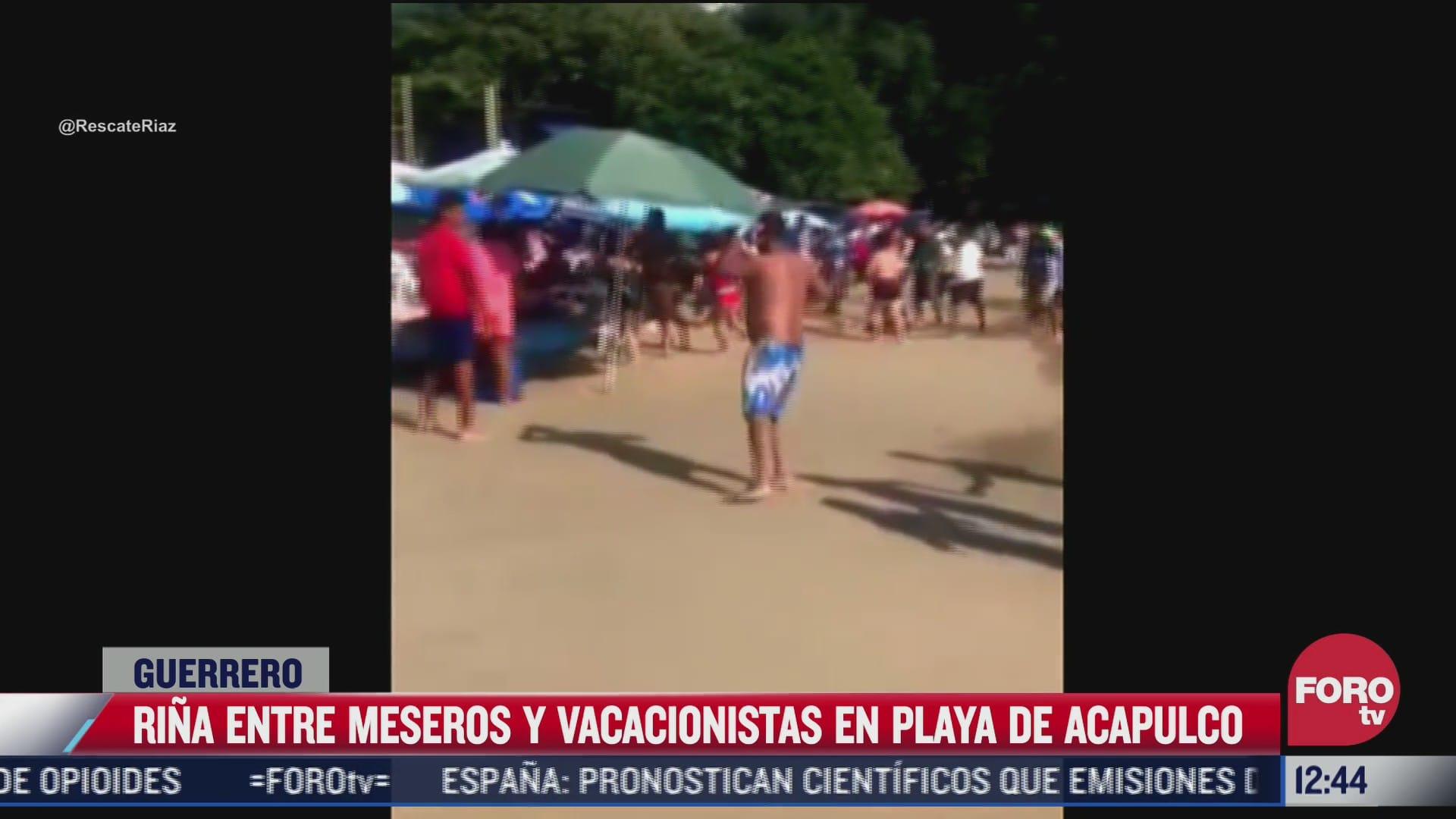 rina entre meseros y vacacionistas en playa caleta de acapulco